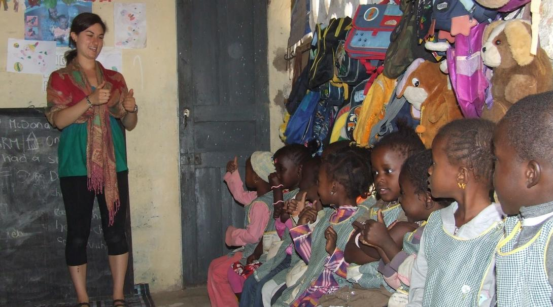 A volunteer works with children in senegal on a project made for teenagers